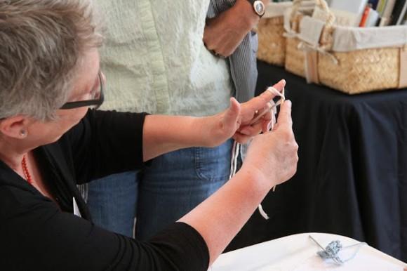 Lisbeth viser en teknisk detalje med to tråde og en pind.
